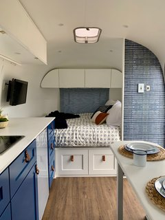 "The couple designed the new layout to include a full bed, which is located on the right upon entering the trailer. Here, ""a privacy wall at the head of the bed creates a nook with a dimmable reading light. Two long sliding drawers underneath the bed allow deep storage in an otherwise unusable space."""