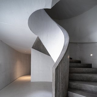 A cement staircase spirals upward to a viewing platform on top of the sand dune, providing visitors with an idyllic setting to take in the vast seaside scenery.