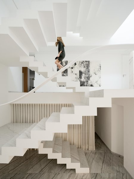 The Mexico City house that Miguel Ángel Aragonés designed for his family contains many of his signature touches, including striking geometries, stark white walls, and rich materials. A work by Jan Hendrix hangs near the home's grand stair.