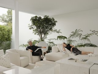 Miguel and his wife, Ana, recline on furniture by Poliform in the home's main living area. The tables are Miguel's own designs.