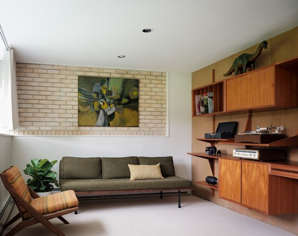 The study features one of a pair of Scissor lounge chairs by Folke Ohlsson for DUX and a vintage wall unit by Poul Cadovius.