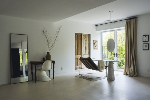 On the home's lower level, an open bedroom area includes a Sierra chair by Croft House and a Nelson Bubble Cigar pendant by George Nelson for Herman Miller.