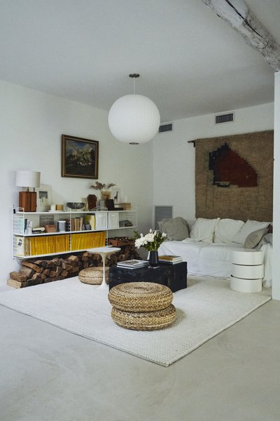 The family room across from the open bedroom features a Nelson Bubble Globe pendant, IKEA Alseda floor stools, and an heirloom tapestry wall hanging.