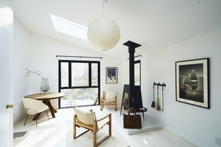 A black-and-white motif is warmed by wood furnishings in the master bedroom of Claire Benoist and Derek Kilner's weekend retreat in Somers, New York. A Shaker stove by Wittus faces a vintage Pierre Chapo table. The windows are by Pella and the fireplace tool set is from Terrain. An Akari ball pendant by Isamu Noguchi hangs overhead.