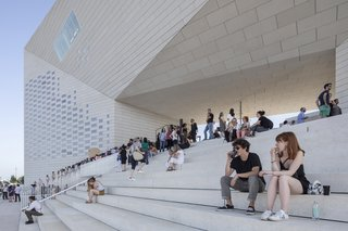 Visitors enjoy MÉCA's cafe offerings as they relax on the steps of the newly opened center.
