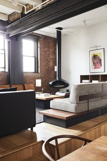 """When OSSO Architecture first began renovating this loft in a Brooklyn paper factory, it hadn't been touched since the 1980s. Owner Malik Ashiru says the project achieved his goal of """"a big, open space where people could come in and not feel cramped."""" The formerly constrained spaces in the 1,400-square-foot, two-story apartment have been reconfigured into an open-plan living space with an office on the first floor and a loft guest bedroom above. On the second floor, the primary bedroom and bath open up to a rooftop terrace. Level changes delineate different spaces in the open-plan first floor, which is stylishly furnished with Ashiru's midcentury furniture and artwork collected from his travels around the world."""
