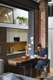 Malik Ashiru and OSSO Architecture rehabbed an apartment that had been unaltered since the 1980s. The old, constricted kitchen gave way to an open space with new Bosch appliances and a sleek wood island. A new steel structure replaces a wall that was removed during the renovation.