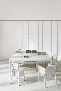 The all-white kitchen/dining area features a custom worktop with integrated sink and a custom dining table on casters, both designed by Simone Subissati Architects. The faucet is by Cea and the cooktops are by Alpes Inox. Around the table are chairs by Piet Hein Eek. A Mexical pendant by Renzo Serafini hangs overhead.
