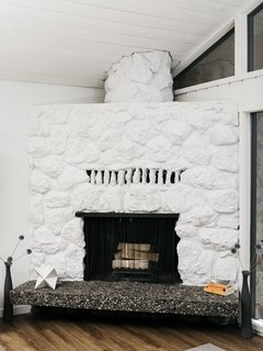 """The lava rock fireplace—which """"smelled like fifty years of shame and cigarettes,"""" says Josh—was refurbished and also painted white. A commercial-grade vinyl plank flooring from Shaw replaced shag carpeting."""
