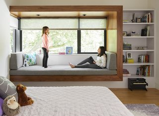 The Patels' daughters, Maya and Ayla, play in Ayla's bedroom, which features a corner window seat framed in walnut. The roller shades are from The Shade Store.
