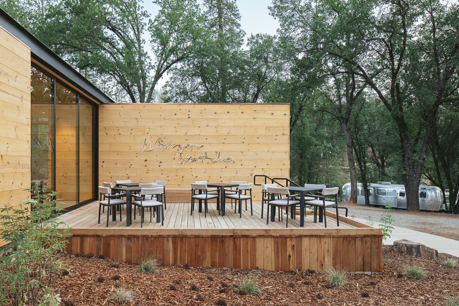 Outdoor, Wood Patio, Porch, Deck, Horizontal Fences, Wall, Shrubs, Wood Fences, Wall, Side Yard, and Trees The patio invites dining alfresco under a neon sign custom-created for AutoCamp.  Photos from AutoCamp's Epic New Location Brings Upscale Airstream Lodging to Yosemite National Park