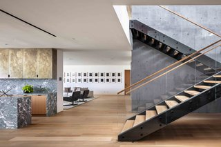 Sleek black steel encases the wooden stair treads that connect the home's three floors.