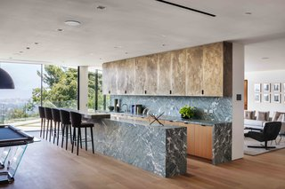 The gourmet kitchen boasts dual marble islands, custom white oak cabinetry, and high-end Gaggenau appliances.