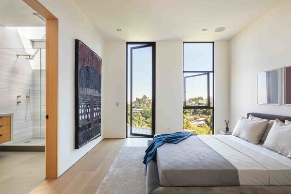 Filled with ample natural light and terrace access, this bedroom also includes an adjoining bath.
