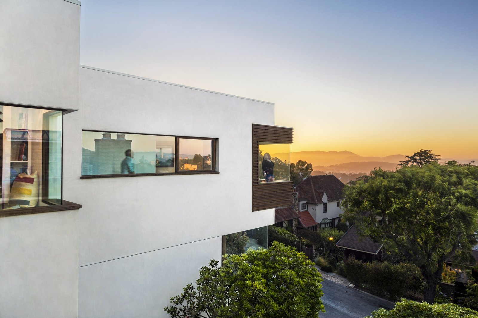 Exterior, Flat RoofLine, Glass Siding Material, Wood Siding Material, and House Building Type The peaked roofline of the original home was flattened, while corner windows take advantage of staggering city views.  Best Photos from Before & After: A Data Scientist Renovates His Childhood Home in San Francisco