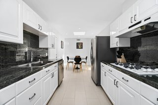 The galley kitchen features crisp white cabinetry with contrasting black accents.