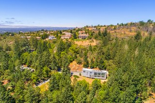 "The approach from a cul-de-sac and down a long driveway reveals the home's horizontal placement along the hillside. Says Whitney Sander, principal and architect, ""As you drive up the hill, you have a feeling there might be a good view to be seen from your destination. Once out of the car, I didn't want to give away the view too soon, so I placed the entry behind the house."""