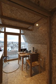 A small dining table is situated near the front door for city views during breakfast or dinner.