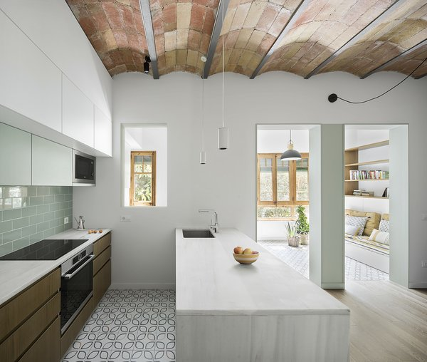 Nook Architects relocated the kitchen from a small space near the entrance to create an open living space for the family of three. A large marble island provides a place to gather.