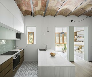 This 720-square-foot apartment in Barcelona was renovated and opened up by Nook Architects. Key to the design are the original barrel-vaulted ceilings, which are mimicked in the mixed-use gallery in the front. What was once a central hallway dividing multiple rooms—typical of older apartments—became a new common space that flows into the gallery. Materials were also limited exclusively to those already present in the space—namely, wood, ceramic, and marble. A canopy of original terra-cotta tiles line the barrel-vaulted ceilings, and a minimal aesthetic ties it all together.