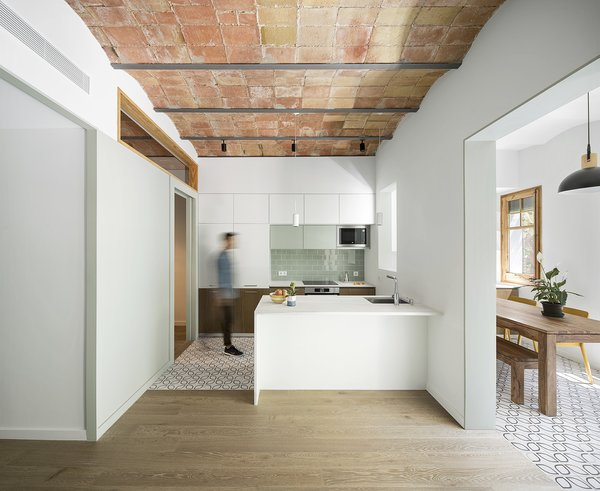 When Nook Architects set out to renovate a 720-square-foot apartment in Barcelona's Poble Sec district, they knew they wanted to retain the space's characteristic elements—especially the original barrel-vaulted ceilings. Here, the track lighting accentuates the rhythmic curves.