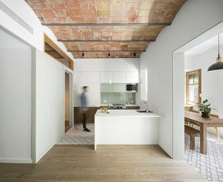 Typical of older apartments, a central hallway once divided the individual rooms. The team opened up portions of the old corridor to create a new common space.