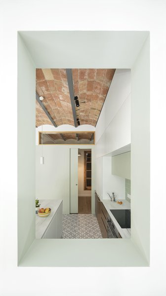 The exposed metal beams and barrel-vaulted ceilings continue into a small bedroom off the kitchen, visible through a new architectural transom window.