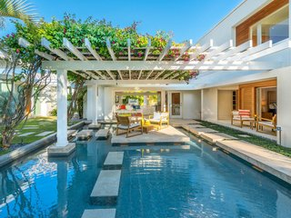 From the driveway, stepping stones lead across a wading pool to the home's main entrance. An island patio rests as a centerpiece beneath the pergola.