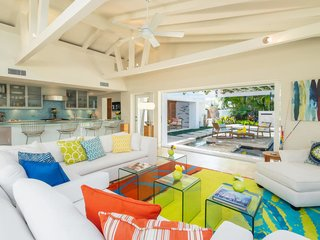 The home's airy living room features floor-to-ceiling windows and sliding glass doors, which open onto the water-wrapped outdoor area.