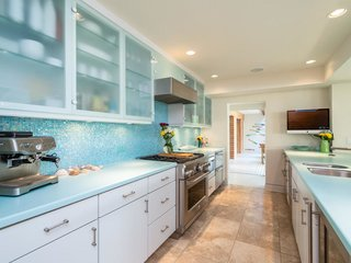 A blue glass mosaic backsplash declares the home's coastal location. The modern kitchen offers professional-grade appliances, custom white cabinetry, and a large peninsula.