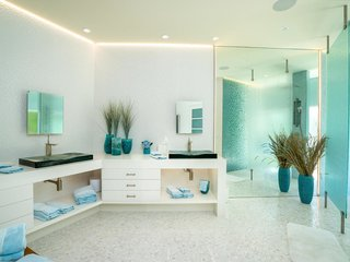 The master bathroom is brightened by custom lighting and natural light shining through the tempered glass shower wall.