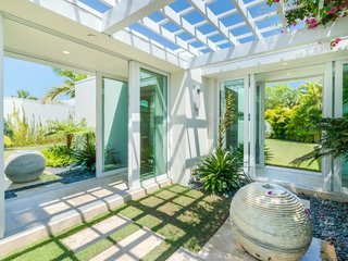 The private walkway has sliding glass doors on all sides, providing access to small garden areas and warm Florida breezes.