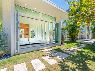At the opposite end of the wing is a sunlit home office, featuring distinct vertical windows and bi-fold doors which open onto the lush landscape.