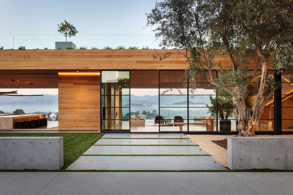 Surrounded by 1.2 acres of flat land, the contemporary residence is designed to frame a unique, long view of Los Angeles—as well as the mountains beyond.