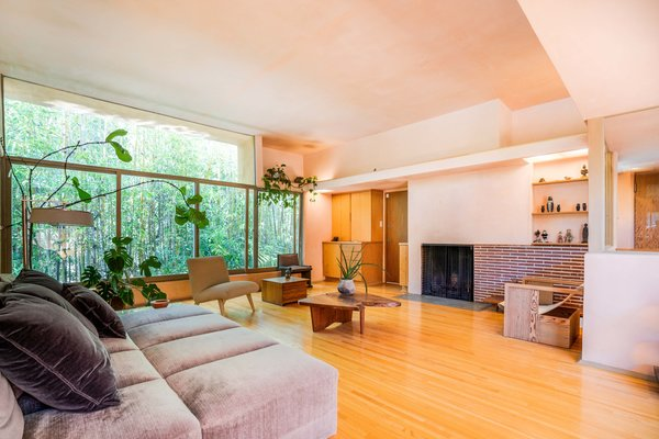 The spacious living room features full-length windows that create a connection with nature. Pink plaster walls were restored to their original condition, as were plywood built-ins.