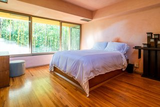 Plays on different forms and shades of natural light continue throughout the two-bedroom home. This bedroom offers a wall of windows and raised ceilings.