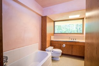 Both bathrooms include modern fixtures while retaining plywood cabinetry. A window extends above the vanity, framing an exterior view in lieu of a mirror.