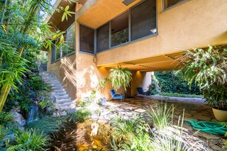 A previous homeowner recreated the open patio and breezeway according to Schindler's original plans. A koi pond with waterfall create an atmosphere of Zen.