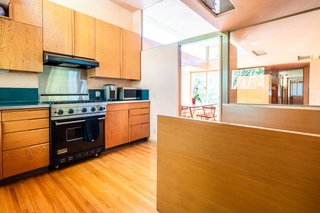 """Sunlight dramatically descends into the kitchen from additional cl<span style=""""font-family: Theinhardt, -apple-system, BlinkMacSystemFont, &quot;Segoe UI&quot;, Roboto, Oxygen-Sans, Ubuntu, Cantarell, &quot;Helvetica Neue&quot;, sans-serif;"""">erestory</span><span style=""""font-family: Theinhardt, -apple-system, BlinkMacSystemFont, &quot;Segoe UI&quot;, Roboto, Oxygen-Sans, Ubuntu, Cantarell, &quot;Helvetica Neue&quot;, sans-serif;"""">&nbsp;windows. The space has been modernized with period-appropriate cabinetry and professional-grade appliances.</span>"""