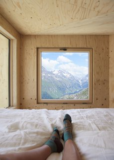 Guests enjoy an unobstructed view of the Engadin Valley from the lofted sleeping area.