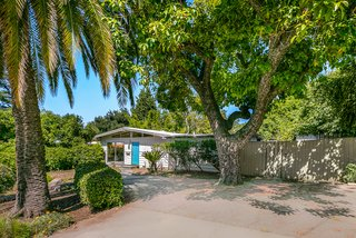 The home is nestled among large trees and lush landscaping, and its simple exterior design still resonates decades later.