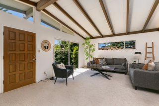 The front entrance opens directly into the main living area. Clerestory windows and a large sliding door bring lots of natural light into the space.