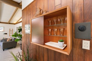 A built-in cabinet with textured glass doors provides storage for extra glassware or supplies for entertaining. The furniture piece is a unique conversation starter in the dining room.