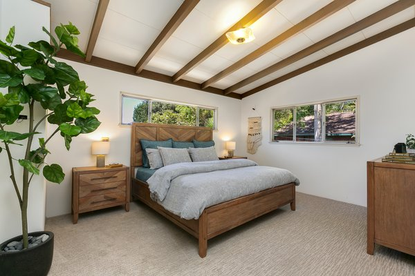 The wood-beamed ceilings continue into the bedrooms, which overlook the quiet yard. New carpeting adds a fresh feeling to the spaces.