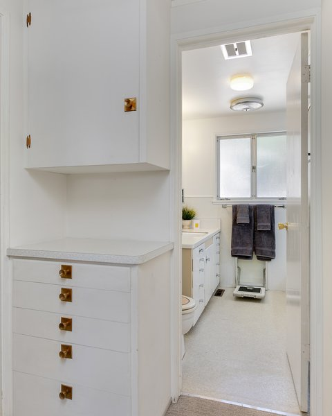 A hallway outside the bathroom includes built-in storage with copper-tone hardware.
