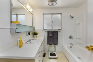 The original bathroom vanity is in excellent condition, with formica countertops and lots of storage. A built-in weight scale is another eccentric period feature of this home.