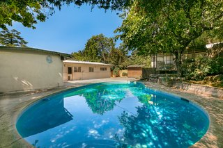 The almost 7,500-square-foot lot features a large in-ground swimming pool and a concrete patio. A separate pool house is adjacent to the main home.