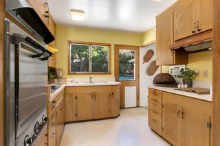 The kitchen is filled with '60s-era features. A built-in AM/FM radio and an electric NuTone grilling station are located along the right counter area.