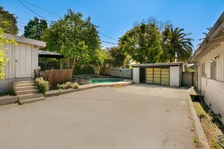 The property also includes a small shed and a two-car garage with direct access to an alleyway.