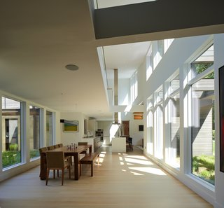 The lower level is lined with walls of glass, including clerestory windows that distribute light throughout the residence.